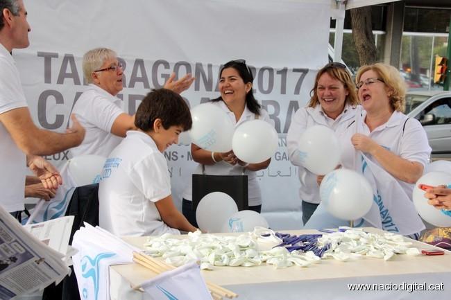 Voluntaris de 2017 inflen globus mentre disposen la paradeta amb material de promoció (foto: naciodigital.cat)