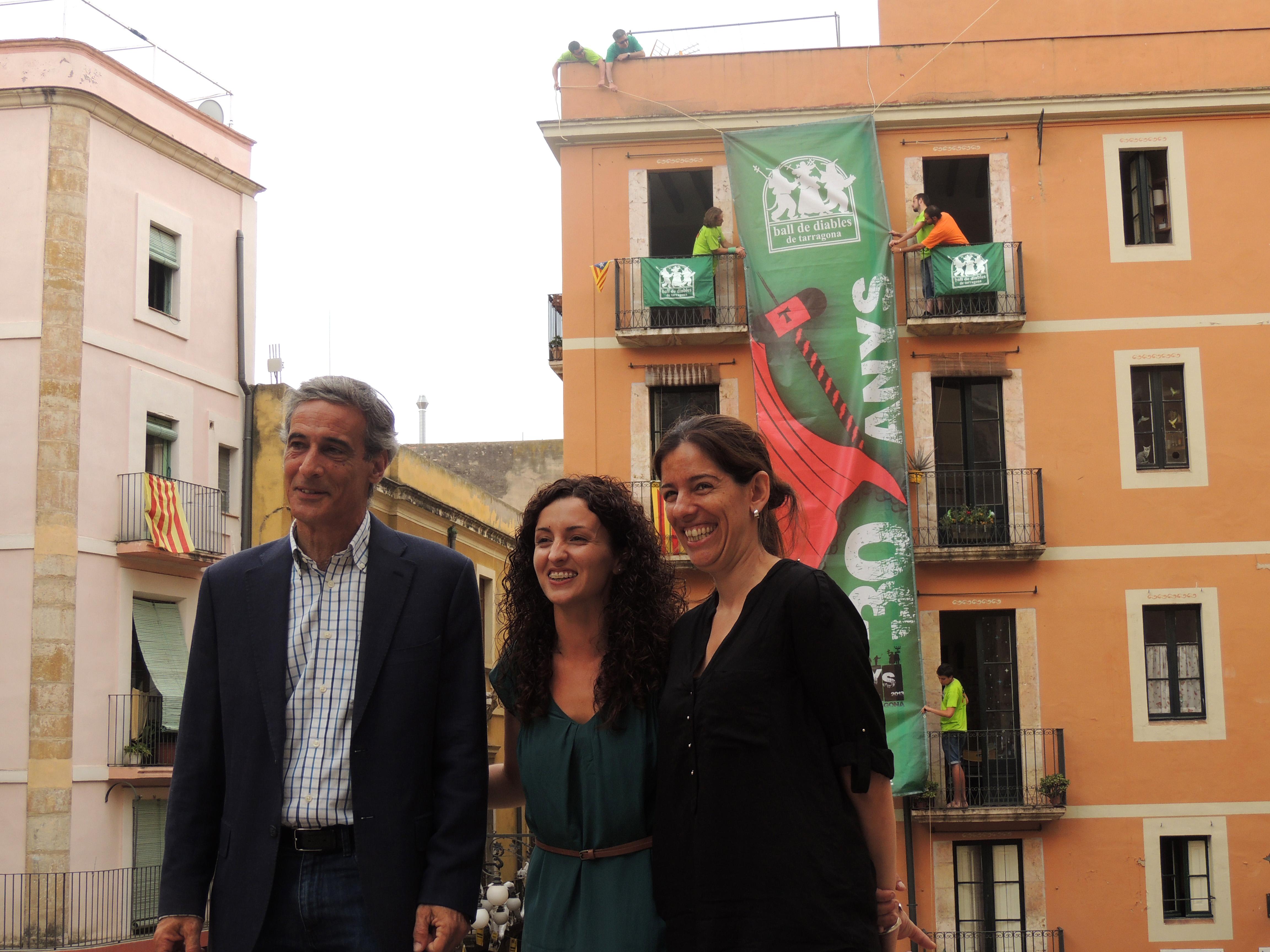 La presidenta del Ball de Diables, Ana Tellaetxe (centre), davant de la lona commemorativa, i acompanyada de Josep Bertran (esquerra), de Repsol, i Marianne Wafelaert (dreta), de Chartreuse Difusion.