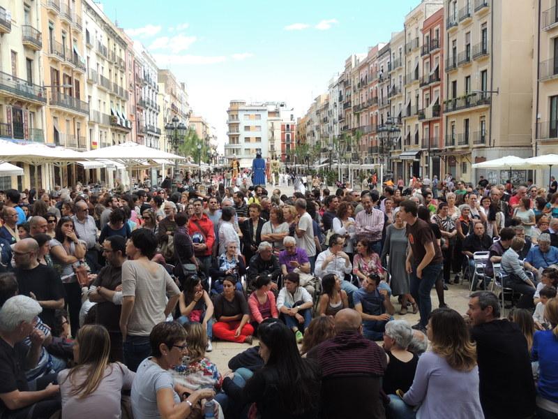 El públic espera a la plaça de la Font, mentre al fons arriben els gegants per participar a la Processó del Corpus