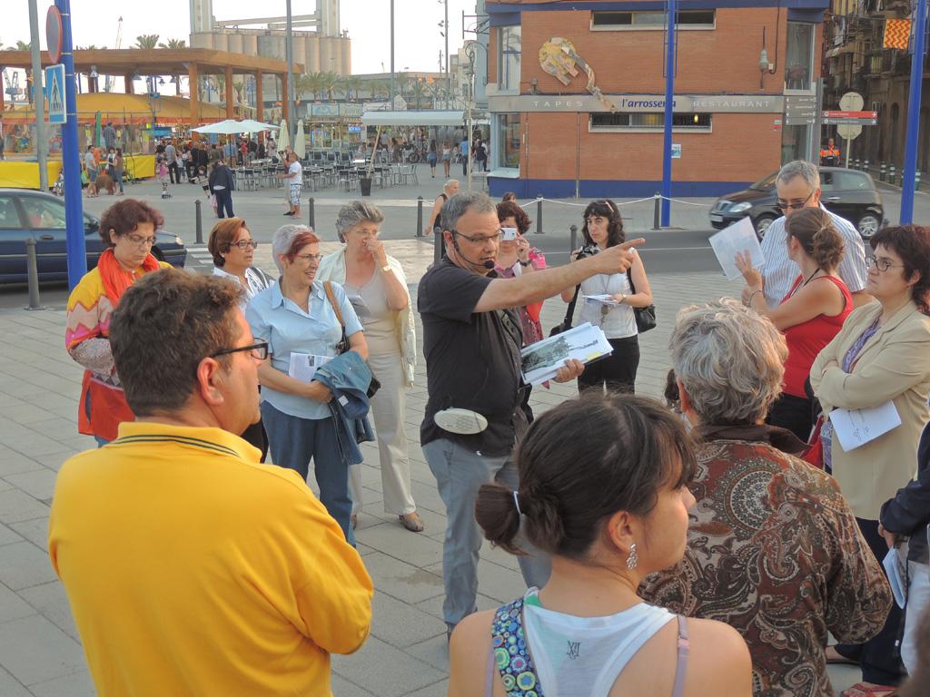 Esteve Masalles explicant la història del Pont de la Petxina. Al darrere, es pot observar la fira de les festes de Sant Pere.