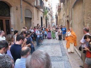 Al carrer de la Destral, una sacerdotissa explica la inscripció que s'hi pot veure (foto: Ivan Rodon- Tarragona Turisme)