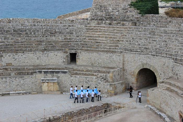 La bandera dels Jocs Mediterranis surt per la Porta Triumphalis