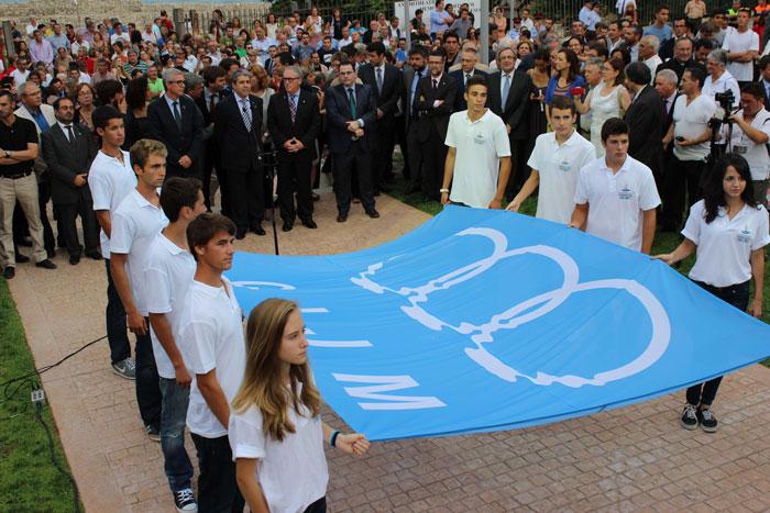 Deu joves esportives de la demarcació porten la bandera i es preparen per hissar-la als jardins de l'Amfiteatre
