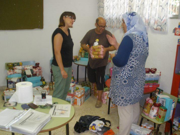 La Natàlia i el Jesús atenen una de les mares de família que van a buscar els aliments