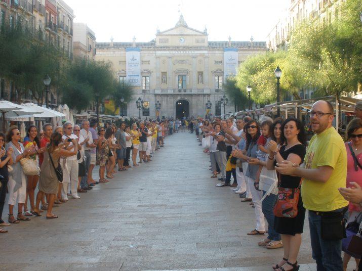 Moment de la cadena humana a la plaça de la Font, amb participants a banda i banda de l'itinerari.