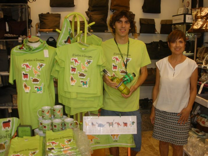 Dani Gros, subscriptor i guanyador del concurs del FET, amb Assumpció Claramunt d'El Negrito i La Negrita a l'interior de la botiga i al costat de les samarretes de les festes d'enguany