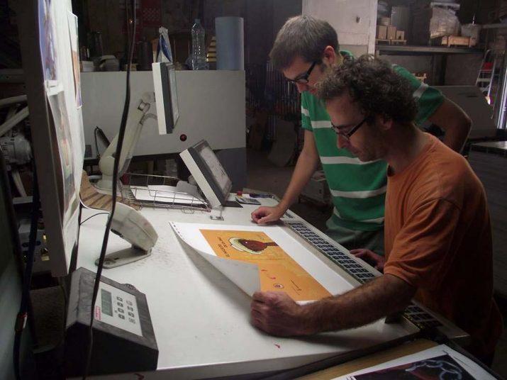 Manel Sanromà, president de l'Associació d'Amics de la Colla Jove, observant la portada, acompanyat de Xavier Salvadó, operari d'Impremtes Gibert.
