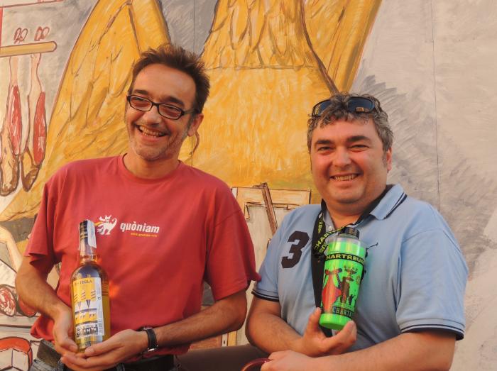 Enric Garriga i Xavier Fortuny, dues persones que s'implicaren activament en el procés de creació de la beguda de les Festes, coneguda popularment com la Mamadeta, sustenten una ampolla de Chartreuse groc i un barrilet.