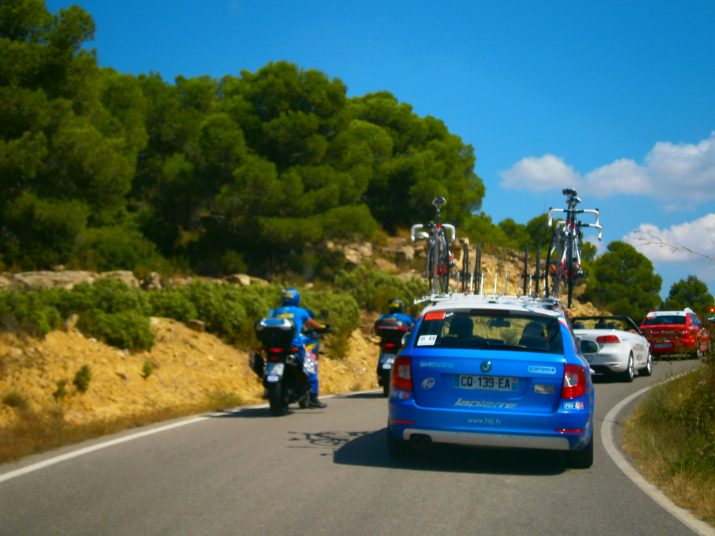 Una llarga cua de cotxes de l'organització, patrocinadors i equips precedix els ciclistes