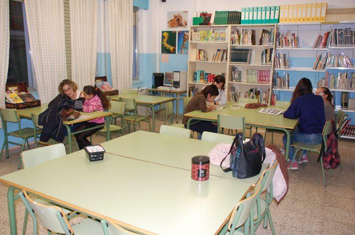 """Tres """"parelles"""" comparteixen lectures a la biblioteca de l'escola"""