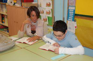"""L'Hugo, de 9 anys, llegeix en veu alta al costat de la seva """"mentora"""", Núria"""