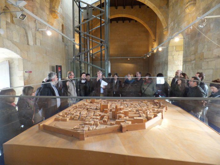 Ruiz de Arbulo, al centre de la foto, amb una carpeta blanca, explica la maqueta de Tàrraco de la torre del Pretori durant la visita amb els subscriptors (Foto Ricard Lahoz)