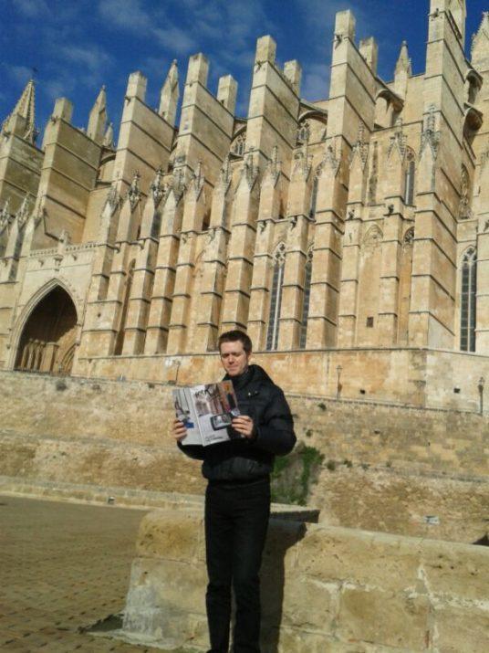 El periodista Jordi Julià llegeix la revista davant la Catedral de Palma de Mallorca