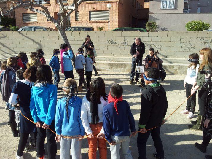 Alumnes de l'escola El Miracle, al pati, escolten la música del clarinet i el violoncel
