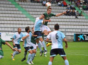 Manu Barreiro lluitant una pilota aèrea en un partit davant del Compos