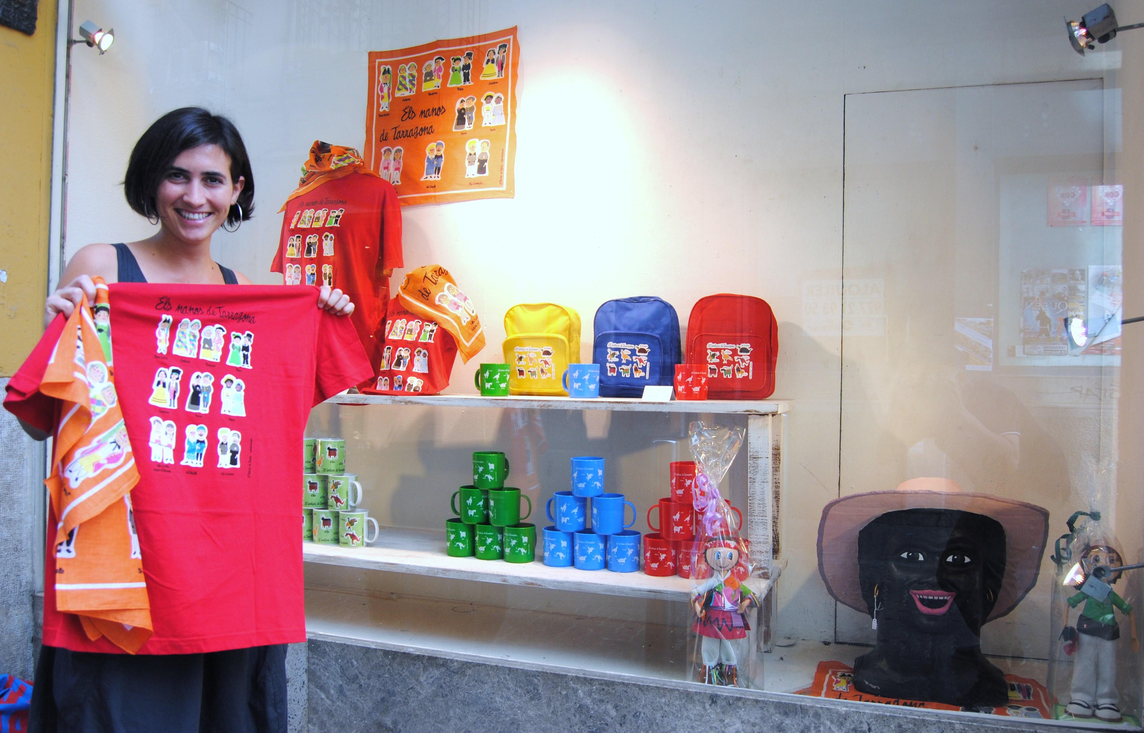 Anna Adsera, nova subscriptora del FET, amb la samarreta i el mocador davant l'aparador de les festes de El Negrito i la Negrita.