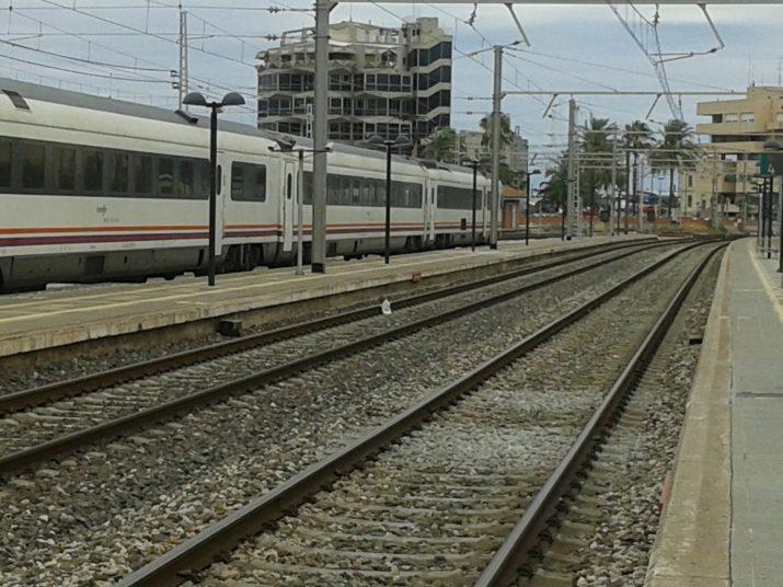 Vies i trens aturats a l'estació de Tarragona. Al fons, l'antiga seu del Port, una de les institucions impulsores del tercer fil