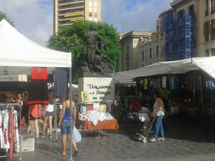 L'Estàtua dels Despullats, qualsevol dimarts i dijous de l'any, envoltada de parades del mercadet ambulant
