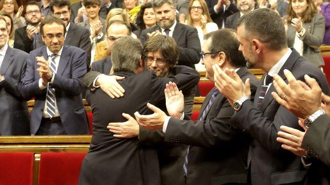 Carles Puigdemont abraçat per Artur Mas, al final de la sessió d'investidura d'aquest diumenge al Parlament (foto: Manolo Garcia)