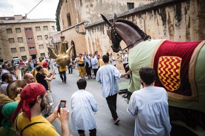 Els membres de l'Àliga i la Mulassa s'intercanvien els elements al carrer de Sant Pau, abans de l'inici de la Professó de Santa Tecla. Foto: DAVID OLIETE