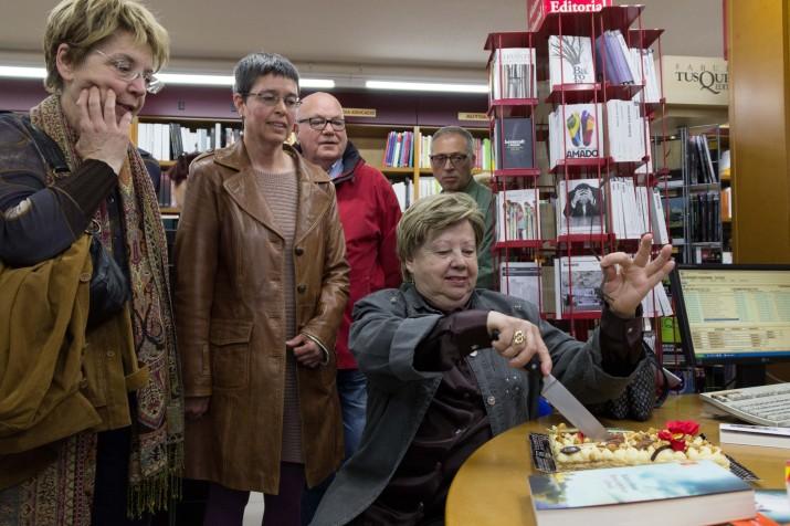 Olga-Xirinacs-talla-el-pastís-de-Sant-Jordi-sota-latenta-mirada-de-Margarida-Aritzeta-i-Cinta-S.-Bellmunt. Foto: LAIA POBLADO