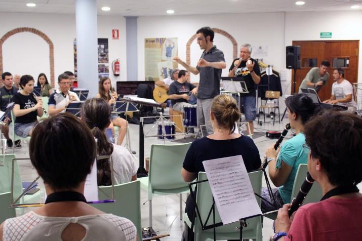 El director de la banda, Òscar Miguel Losada, dirigeix l'assaig del concert amb Quico el Cèlio, el Noi i el Mut de Ferreries. Foto: BUMT