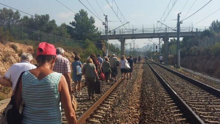 Passatgers caminant per les vies després d'una de les múltiples incidències a la xara ferroviària tarragonina. Foto: Carme Gaseni @kgaseni