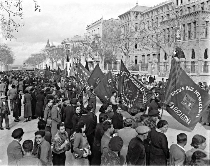Manifestació a favor de la creació d'un exèrcit regular, passant per davant de la Casa del Poble, convent de les Teresianes, a la Rambla 14 d'abril, 8 de març de 1937. Destaca el mural de Stalin en la façana de l'actual col·legi. Foto Vallvé. CIT / L'Arxiu